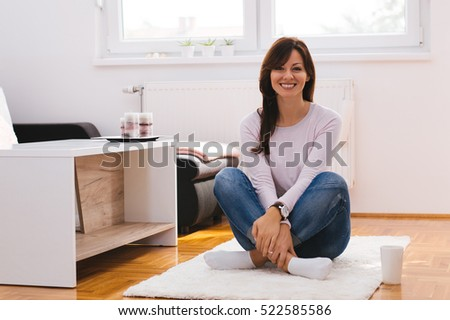 Girl moving in a new apartment, sitting on the floor, looking happy.