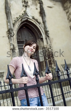 Girl near an iron fence of a Gothic Cathedral - stock photo