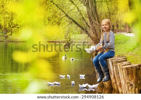 Girl near pond playing with paper boats in forest - stock photo