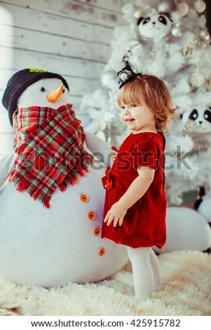 girl near the Christmas tree and snowman - stock photo