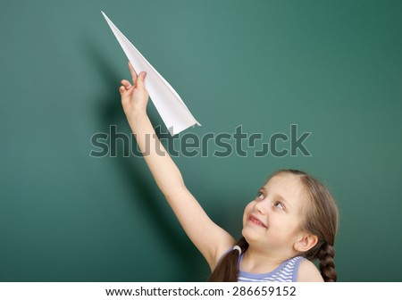 Girl near the school board with paper airplane