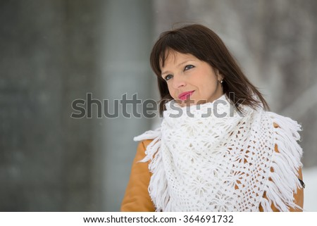 girl near the snow-covered spruce in high spirits