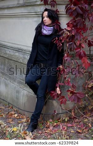 Girl near the wall in the autumn park - stock photo