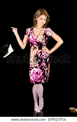 Girl-next-door beauty in colorful spring outfit dropping a shoe. - stock photo