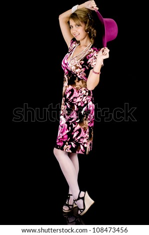 Girl-next-door beauty in colorful spring outfit removing her hat seductively. - stock photo