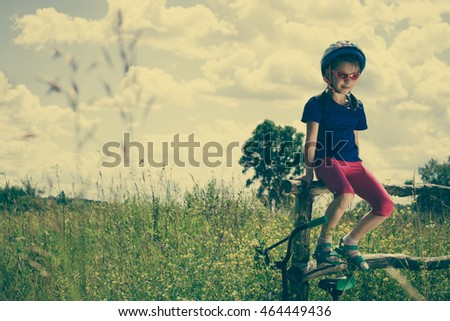 Girl next to a bicycle.