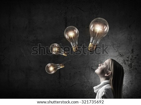 Girl of school age looking above at light bulb