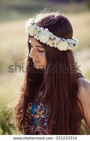 Girl on a beautiful field on with a flower garland on a summer day - stock photo