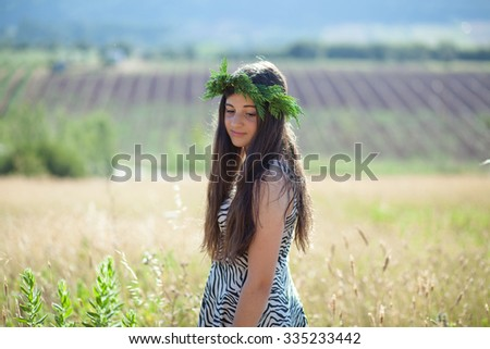 Girl on a beautiful field with a flower garland on her hair on a summer day - stock photo