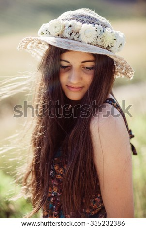 Girl on a beautiful field with a sunhat on a summer day - stock photo