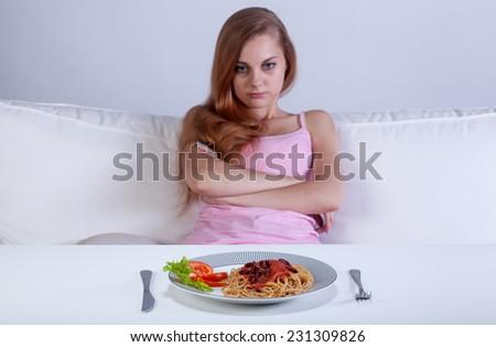 Girl on a diet refusing to eat dinner - stock photo