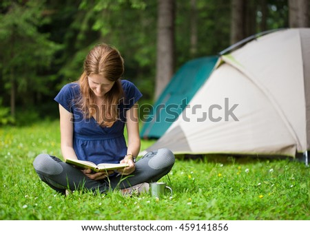 girl on a rest with book sitting near a hiking tent on a forest lawn