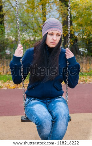 girl on a swing in the autumn park - stock photo