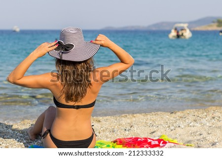 Girl on a tropical beach with hat. - stock photo