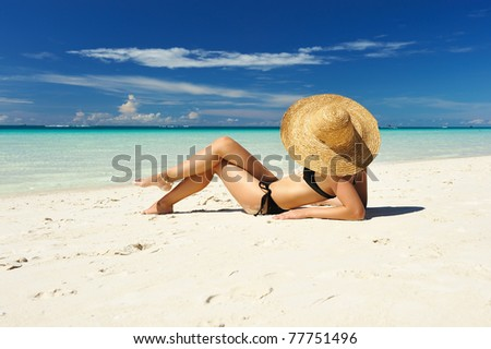 Girl on a tropical beach with hat