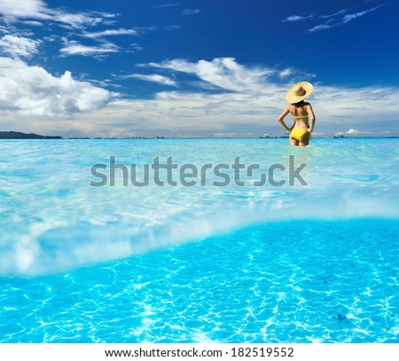 Girl on a tropical beach with white sand bottom underwater and above water split view - stock photo