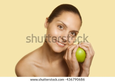 girl on a yellow background holding an apple in his hand