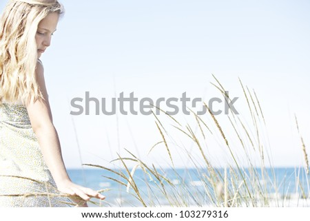 Girl on beach turning and touching long grass against a blue sky. - stock photo