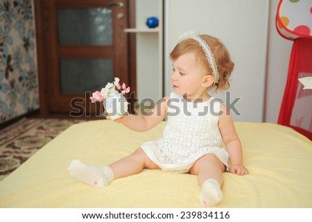 girl on bed holding vase with flowers - stock photo