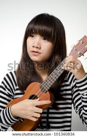 Girl on black and white shirt play ukulele - stock photo