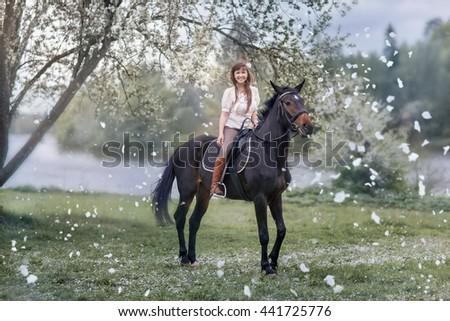 Girl on black horse in blossom garden - stock photo