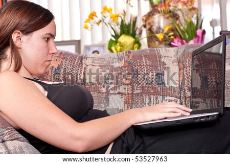 Girl On Couch Surfing the Web - stock photo