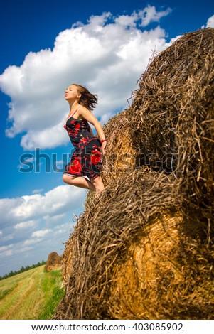 girl on hay, dress, country landscape, round haystack,  field summer day - stock photo