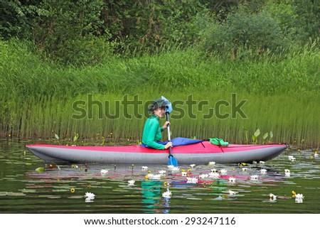 girl on kayak among water lilies(nymphaea, nuphar), river Vetluga, Russia - stock photo