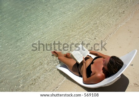 Girl on lounger reading by tropical sea - stock photo