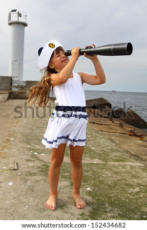 Girl on pier at sea looks through spyglass - stock photo