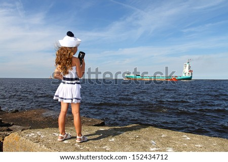 Girl on pier at sea with a spyglass looks at ship - stock photo