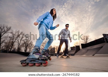 Girl on rollerblades and boy on skateboard in skate park - stock photo
