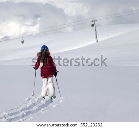 Girl on skis in off-piste slope with new fallen snow at nice day. Caucasus Mountains, Georgia, region Gudauri.