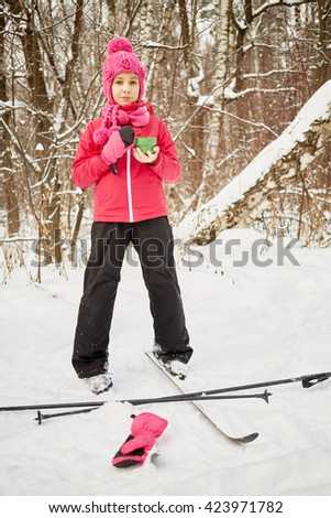 Girl on skis stands in park with cup of tea in hands.
