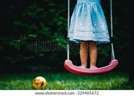 Girl on swing in grass lower legs crop - stock photo
