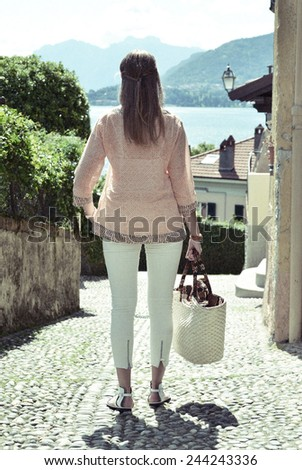Girl on the cobbled street of Menaggio town. Lake Como, Italy -- retro nostalgic filtered look - stock photo