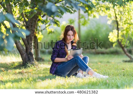 Girl on the grass in the garden with your tablet