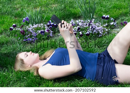 Girl on the grass playing with electronic tablet - stock photo