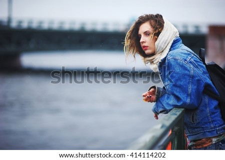 Girl on the quay in the rain standing near the railing  - stock photo