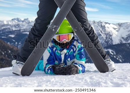 Girl on the snow under the ski