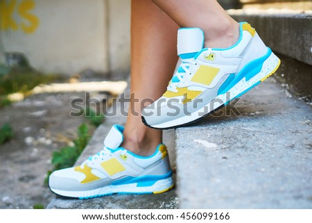 Girl on the stairs wearing sports shoes, model posing in the street, fashion trends - stock photo