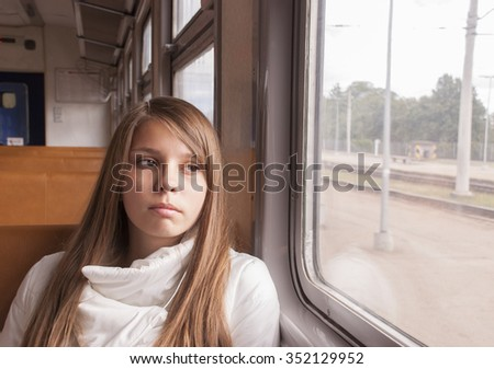 Girl on the train looking out the window - stock photo