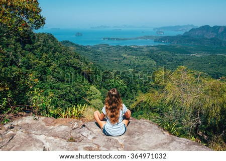 Girl on the view point of the mountain, sitting back to the camera, concept of freedom and traveling. Traveler enjoying the landscape from mountain in Tab Kak Hang Nak Nature Trail, Krabi, Thailand - stock photo