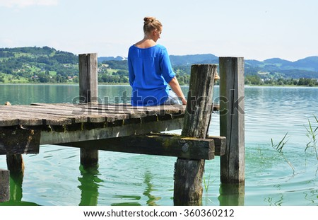 Girl on the wooden jetty. Switzerland - stock photo