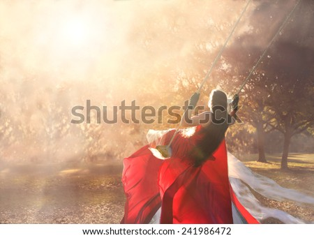 Girl or young woman swinging outside in long formal gown dress with long brown hair looking off into the distance with sun beaming down on her in a magical mystical fantastical way - stock photo