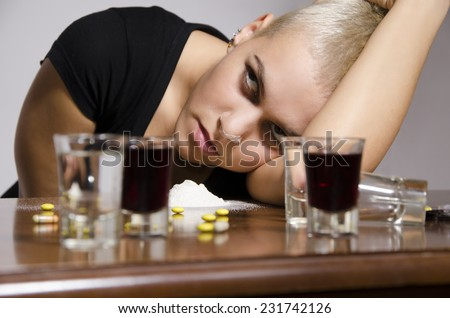 Girl overdosed surrounded with drugs and alcohol - stock photo