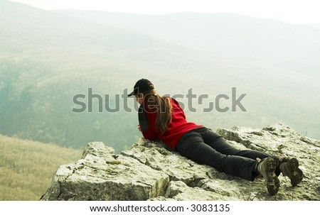 Girl overview landscapes on rock - stock photo