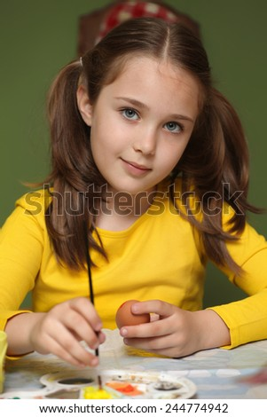 Girl painted Easter eggs at the table - stock photo