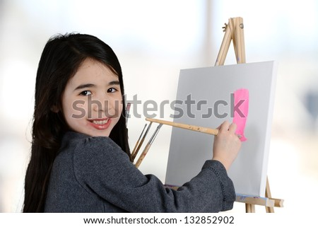 Girl painting a canvas while at school - stock photo