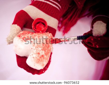 Girl painting snow heart in red water color. Outside in the winter. - stock photo